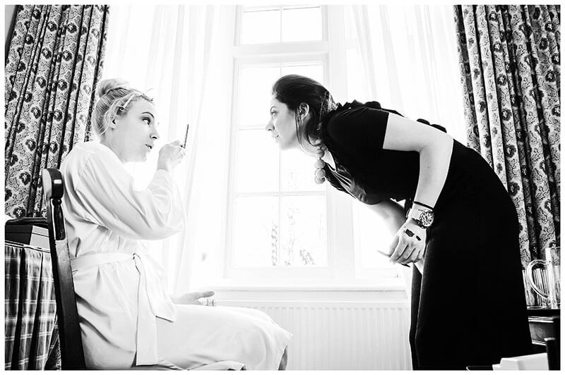 Bride and make up artist checking out brides make up in front of large window