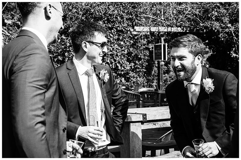 groom laughing with male guests in pub garden