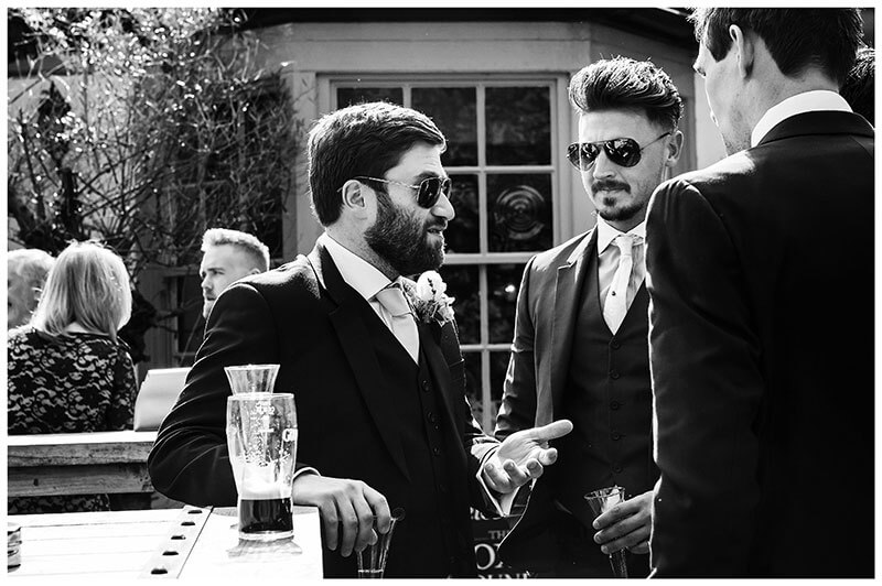 groom wearing sunglasses leaning against table in pub garden talking and gesturing to male guests