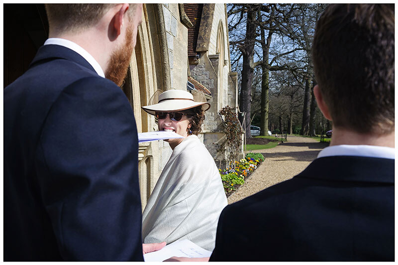 Lady enters Royal Chapel Windsor Great Park with order of service in mouth