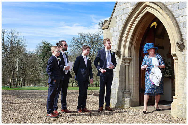 Lady in blue holding white bag in entrance of Royal Chapel Windsor Great Park four ushers stand outside