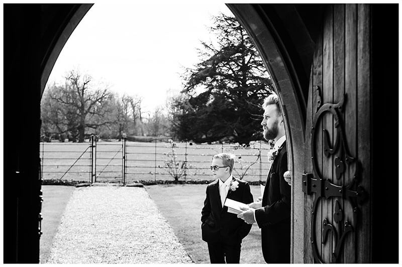 Two ushers standing outside Royal Chapel Windsor Great Park viewed from inside chapel through door
