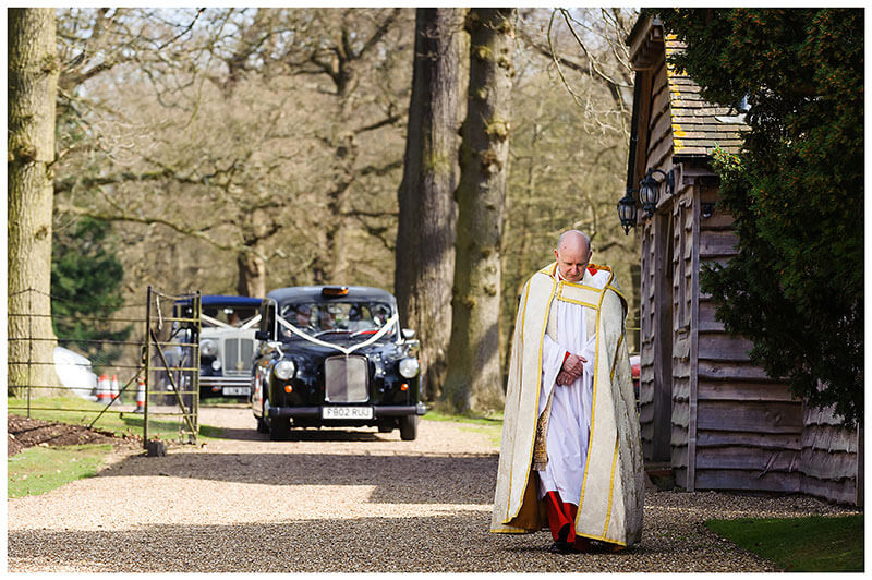 The Royal Chapel Windsor Great Park Bishop head bowed leads the wedding cars a black cab and rolls royce towards the chapel
