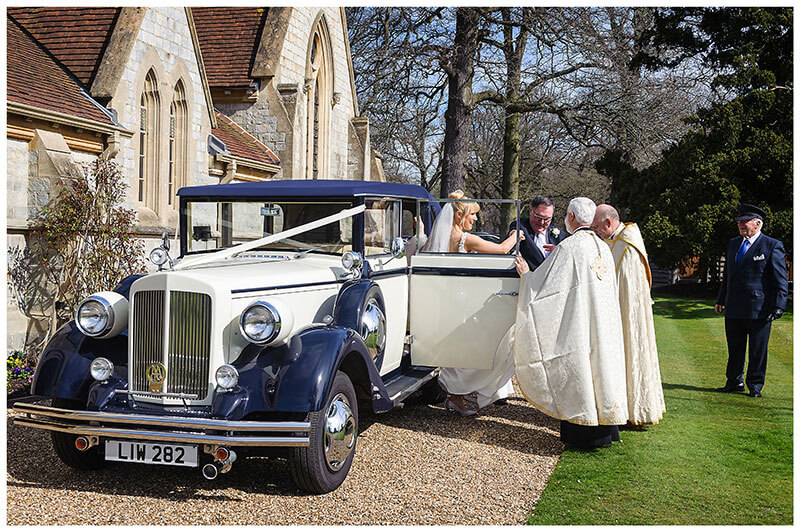 Bride is helped out of wedding car by her father and Royal Chapel Windsor Bishop and Greek Orthadox Bishop car drive watches in background