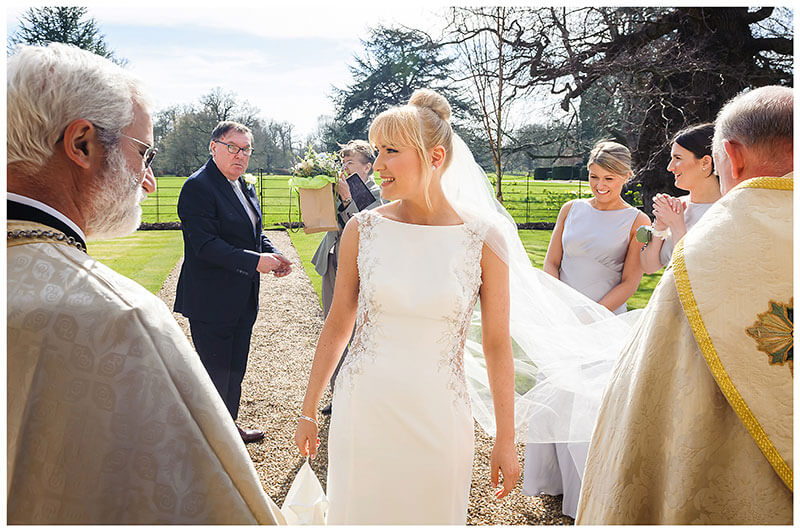 Bride waits to enter Royal Chapel Windsor Great Park surrounded by two bishops and bridal party