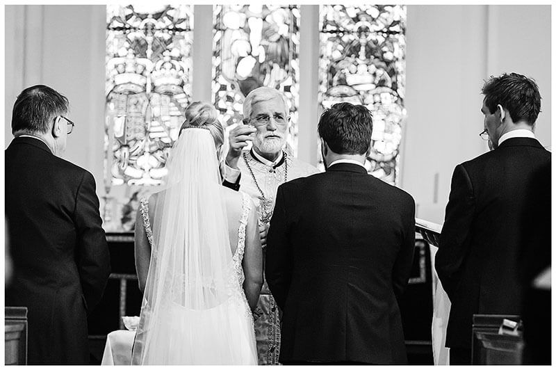 Showing of wedding bands during Greek Orthodox portion of wedding ceremony at lower girl distracted during wedding ceremony at Royal Chapel Windsor Great Park