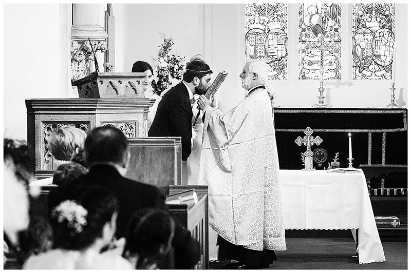Groom kisses the bible during greek orthodox wedding ceremony at Royal Chapel Windsor Great Park