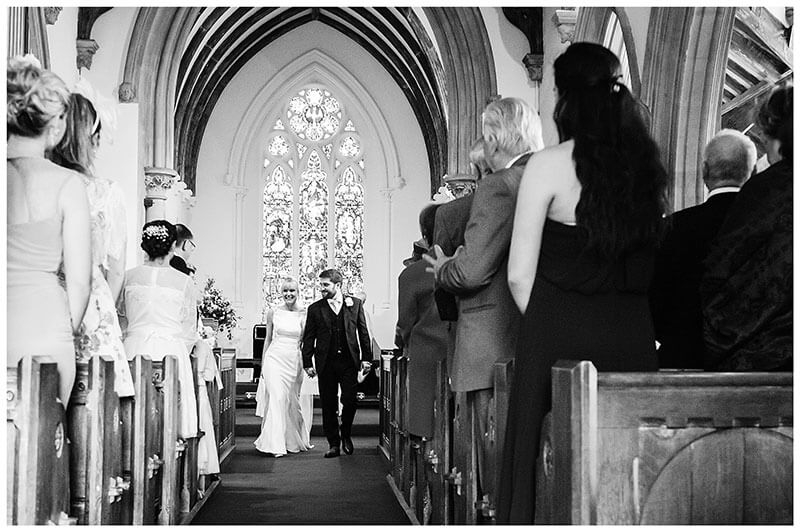 Smiling Bride Groom walking down aisle hand in hand at Royal Chapel Windsor Great Park