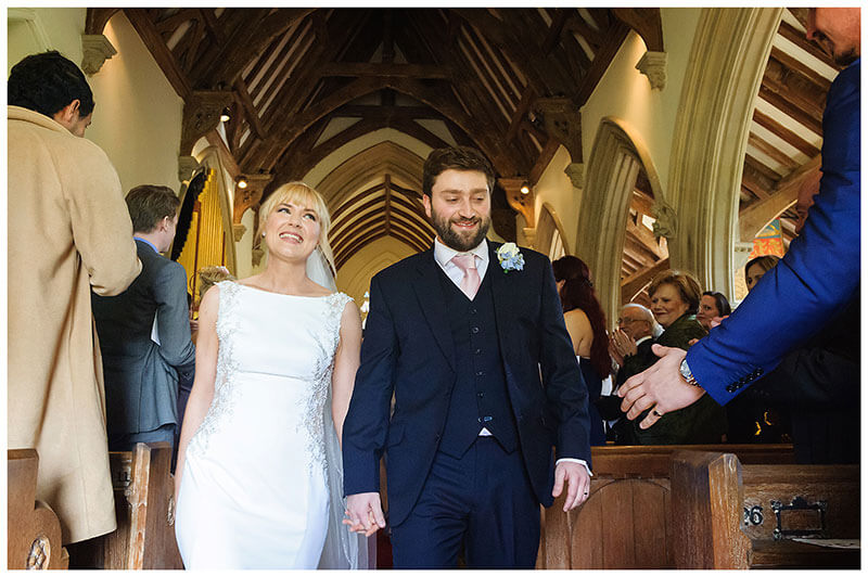As bride and Groom walk down aisle male guest reaches out to shake grooms hand at Royal Chapel Windsor wedding