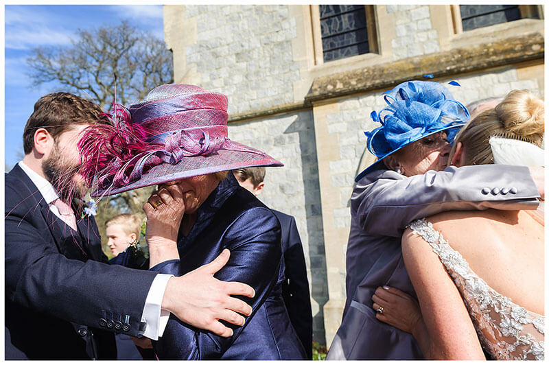 Tearful Bride grooms mothers hug the happy couple at Royal Chapel Windsor  wedding