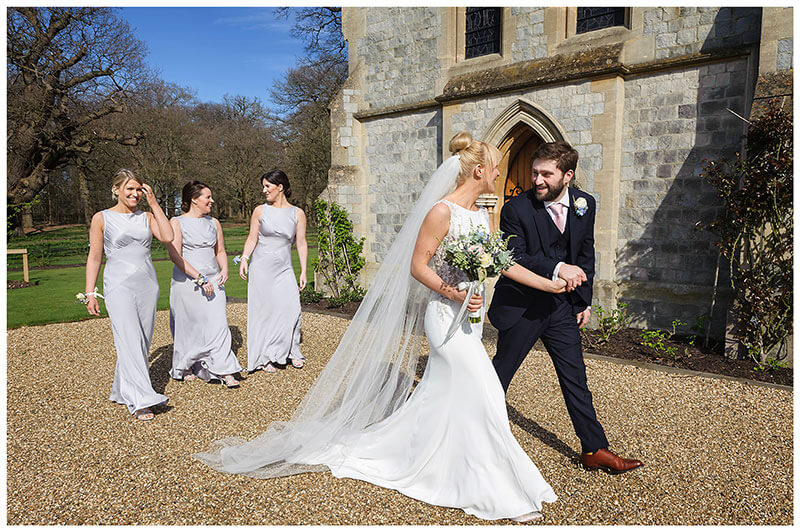 Joyfull bride groom walking hand in hand outside Royal Chapel windsor followed by the three bridesmaids