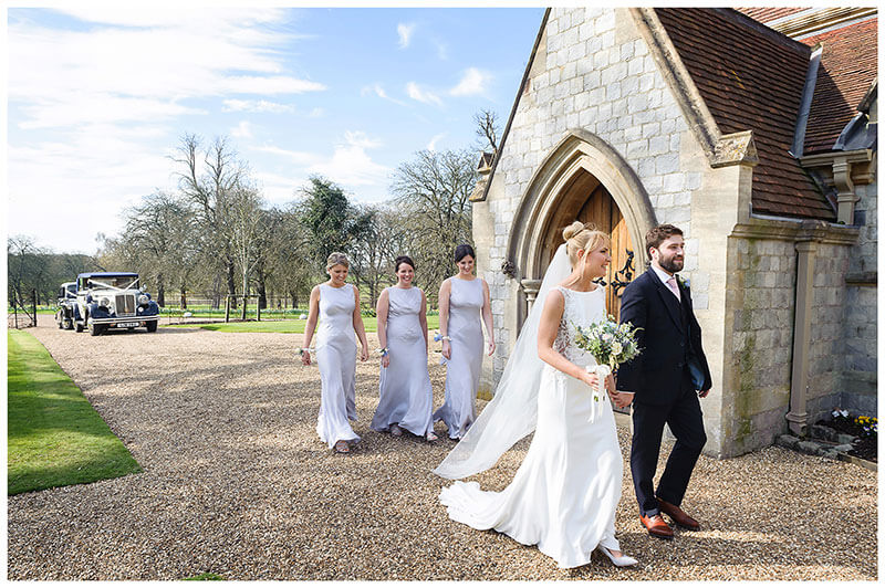 Bride groom walking in front of royal chapel windsor followed by bridesmaids with wedding cars in background