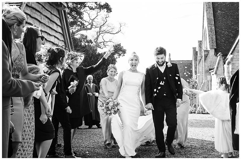 Guests start to throw confetti at joyful bride and groom at Royal Chapel Windsor wedding