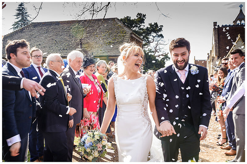 laughing bride and groom during confetti throwing at Royal Chapel Windsor  wedding