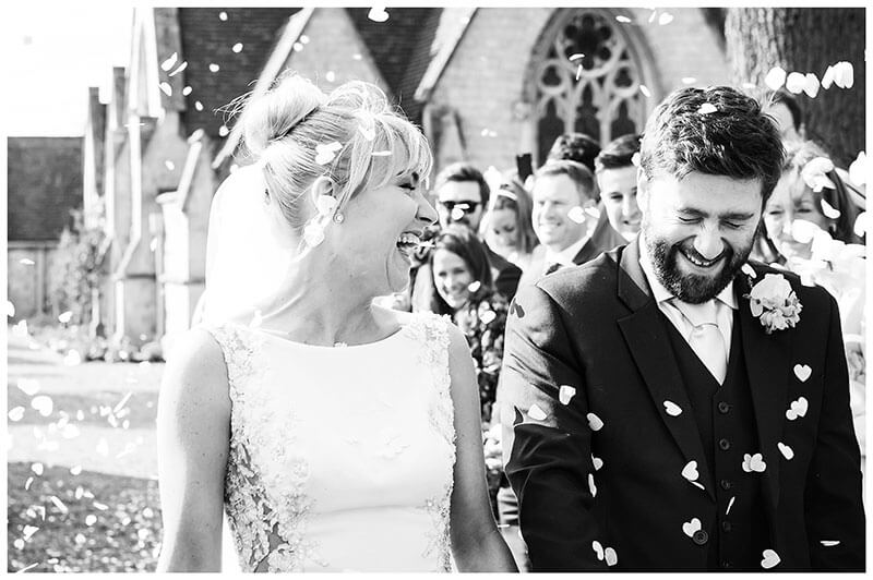 Groom closes eyes as bride laughs during confetti throwing with Royal Chapel Windsor Great Park in background