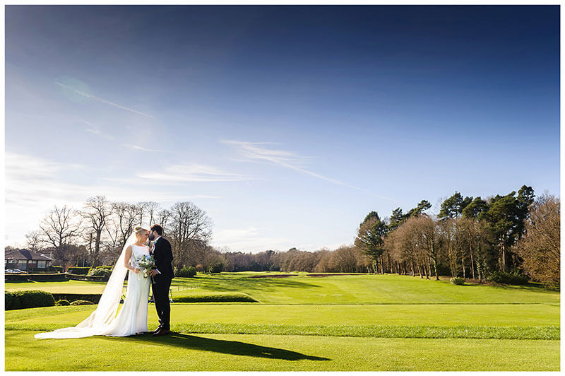 Groom kisses brides forehead on the first tee at the famous Wentworth Club Surrey