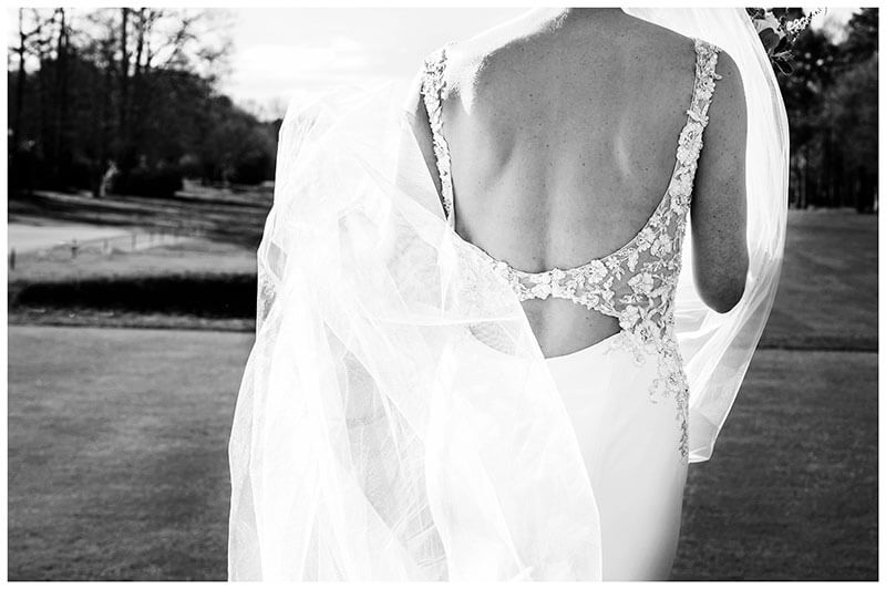 Back of Brides dress with her veil starting to wrap its self around the bride
