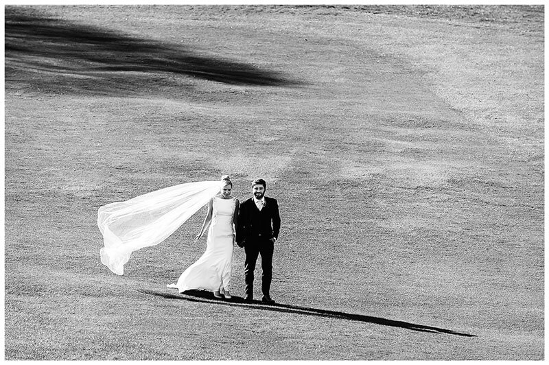 Brides veil blowing in the wind as she and her groom walk hand in hand on Wentworth Club golf course fairway