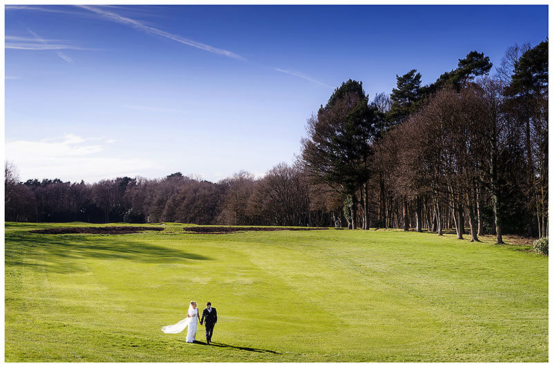 Bride holds her viel as she looks at her groom walking down the Wentworth Club golf course fairway