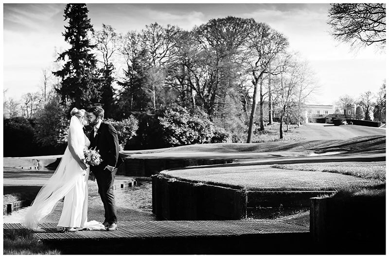 Bride groom kiss standing on a bridge on Wentworth Club golf course