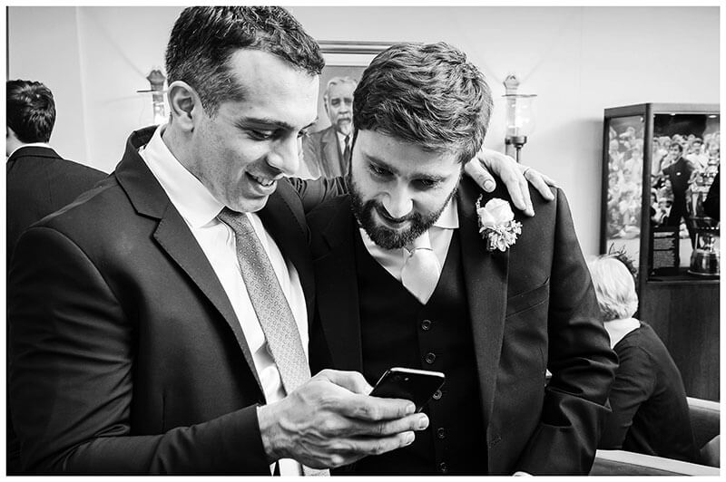 Male guest embraces groom to show him a photo on his phone