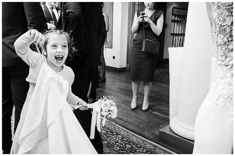 Flowergirl laughing as she plays with brides dress
