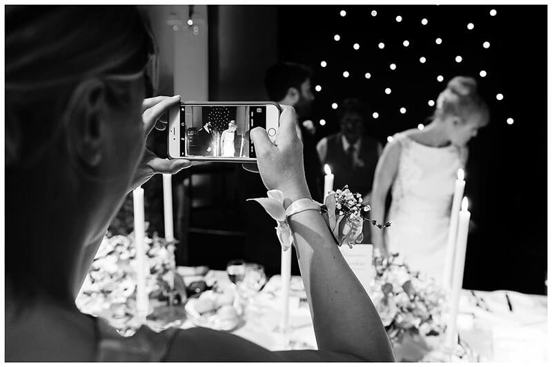 Taking a photo on her phone of bride groom