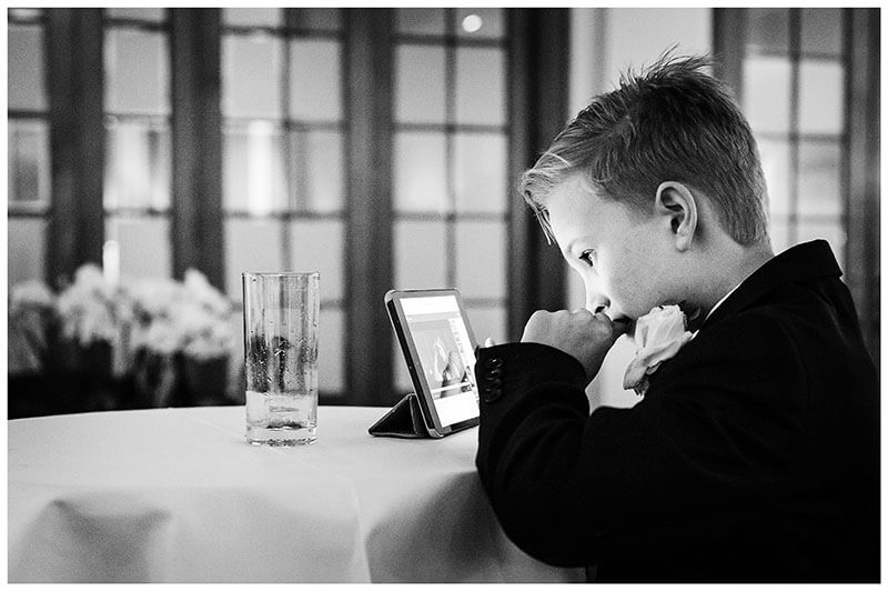Young wedding guests watching a movie on an ipad during the reception