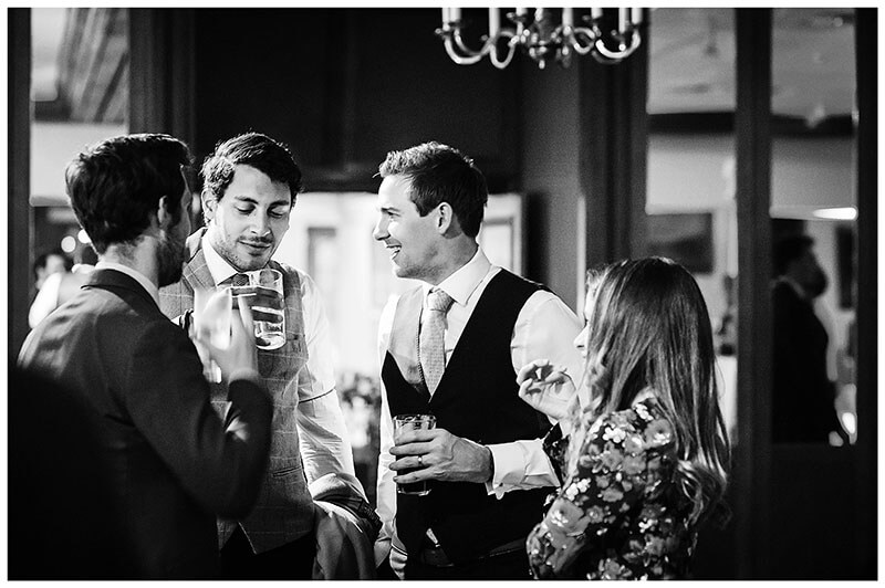 Guests enjoying conversation and a drink during wedding reception at Wentworth Club golf course