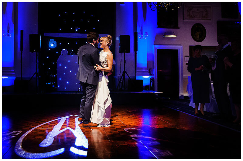 smiling Bride dancing first dance with groom at Wentworth Club golf course heart shape light on dance floor