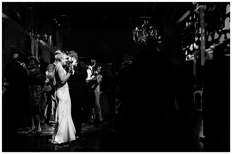 Bride groom bathed in light as they are jioned by their wedding guests on the dance floor