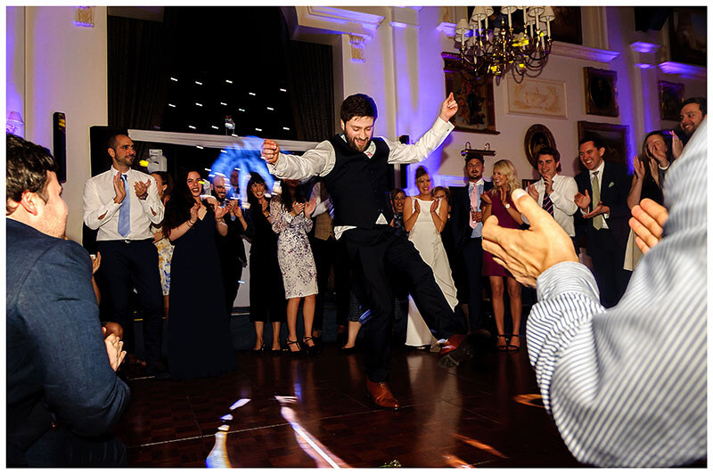 Groom surrounded and encouraged by guests shows off his greek dancing skills