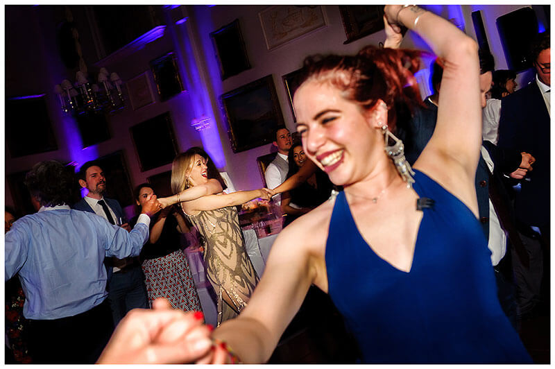 dancing in a circle smiling wedding guests