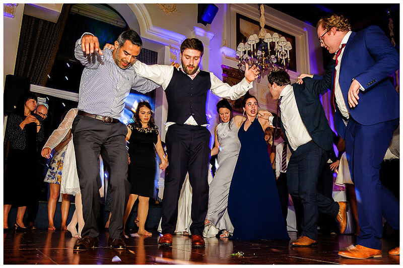Groom and gent greek dancing surrounded by guests
