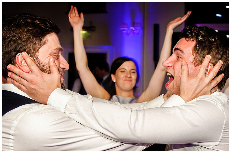 groom and male guests on the dance floor embrace each other heads female arms raised
