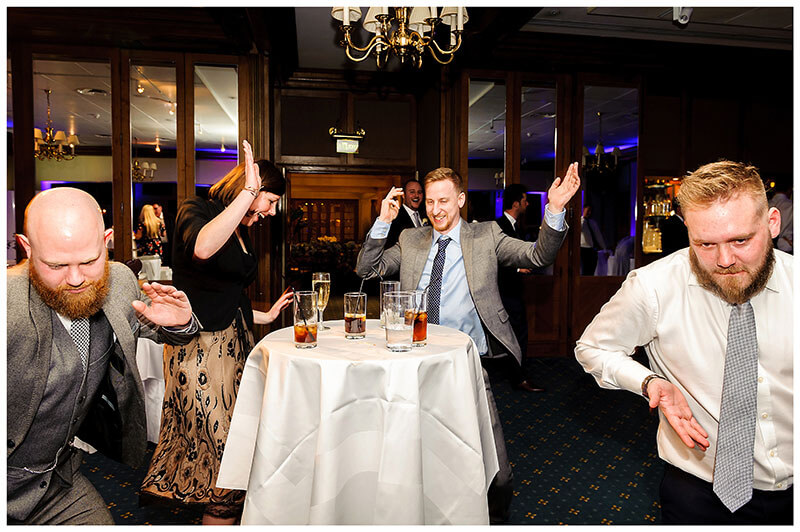 wedding guests dancing around bar table