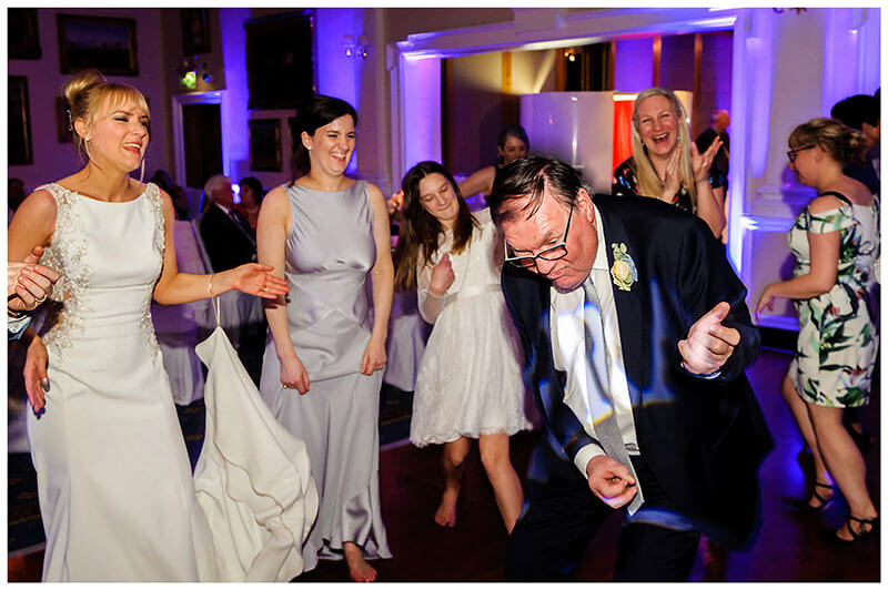 father of the bride playing air guitar on the dance floor