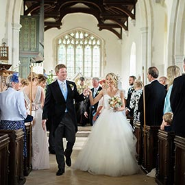 bride & Groom smiling walking down aisle hand in hand after Cambridge village wedding ceremony