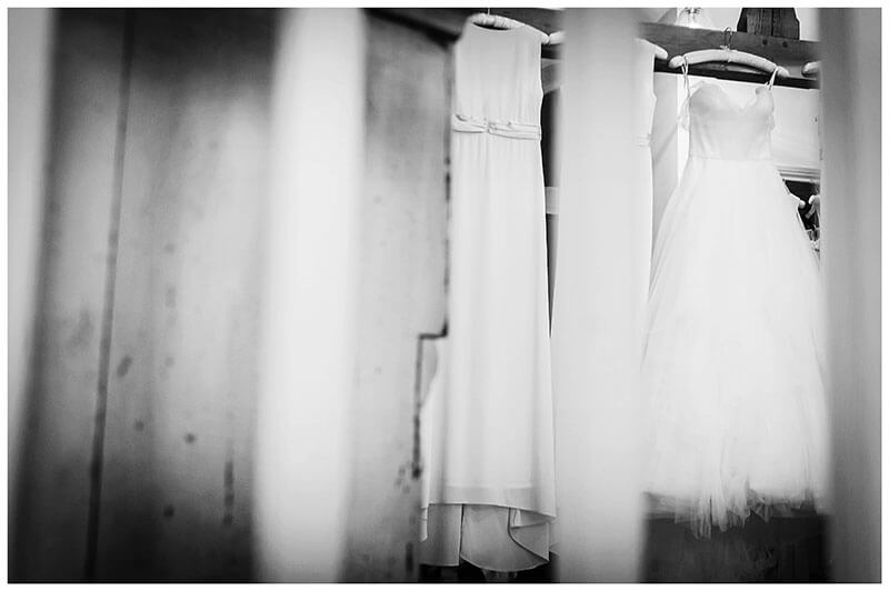 Brides dress hanging next to bridesmaids dress veiwed through stair railings