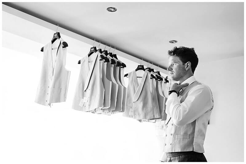 Apprehensive groom adjust tie waitcoats hanging from railing