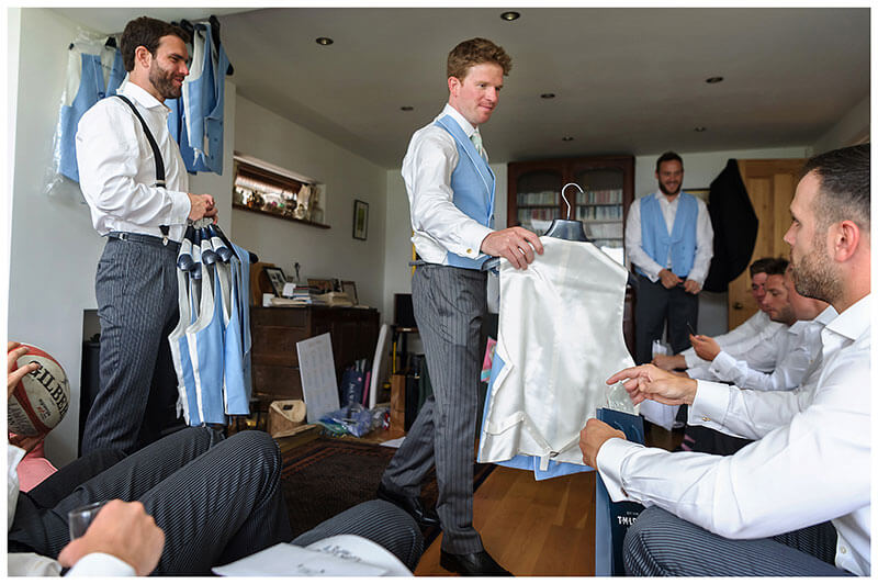 groom handing out waistcoats to ushers
