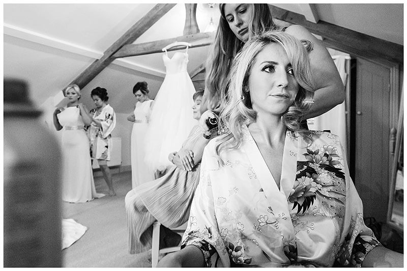 Bride getting hair done bridesmaids helping each other with thier dresses in background