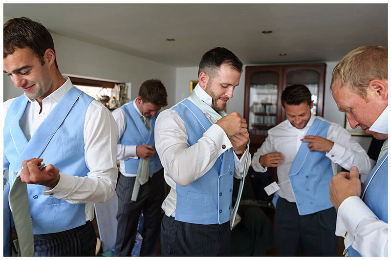 all the guys getting their waist coats on and ties down up