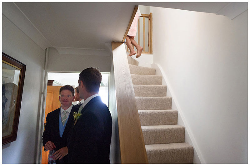groom about to leave home for the ceremony as mother goes up stairs