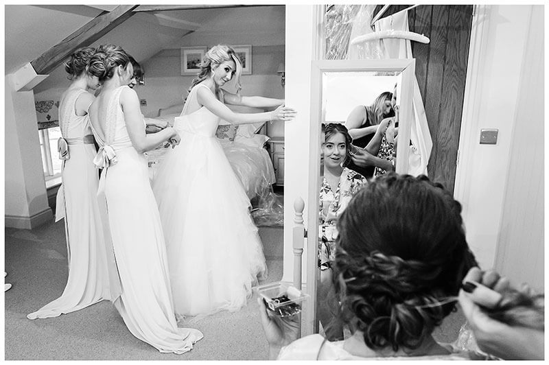 Bride leans against wall as she is helped into her dress by bridesmaids other bridesmaid getting ready reflected in mirror