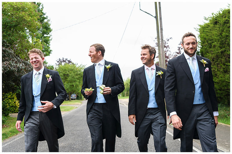 Groom embarrassed as he walks along road with ushers