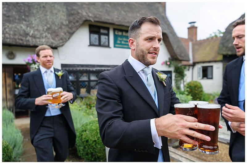 groomsmen getting the beers in at the pub Chrishall Village Wedding