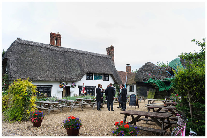 Groom and ushers outside pub in Chrishall Cambridgeshire Village