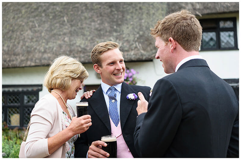 laughing with groom outside pub in Chrishall Cambridgeshire Village Wedding