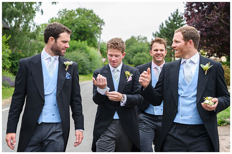 Groom adjust cufflink as he walks with ushers through Chrishall Village in Cambridgeshire